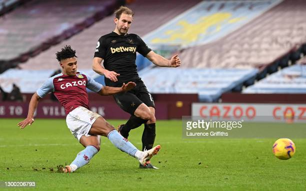 Ollie Watkins of Aston Villa scores their side's first goal whilst under pressure from Craig Dawson of West Ham United during the Premier League...