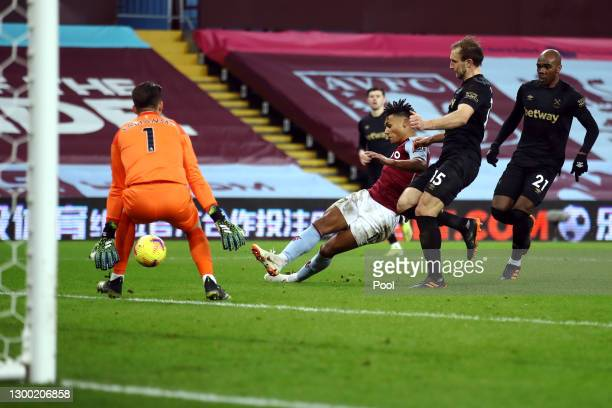 Ollie Watkins of Aston Villa scores their side's first goal whilst under pressure from Craig Dawson and Angelo Ogbonna of West Ham United during the...