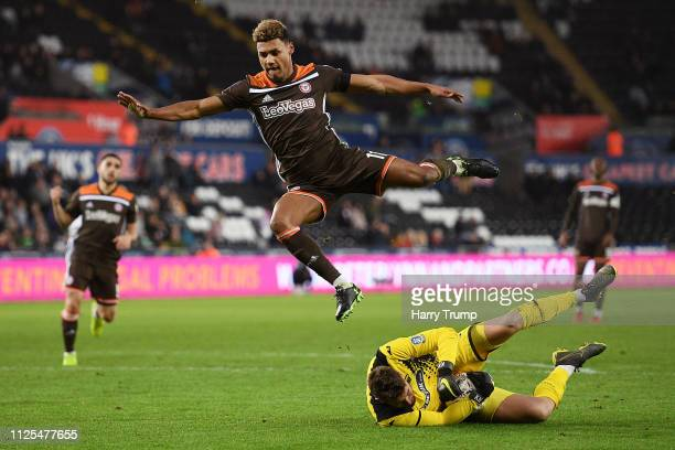 Ollie Watkins of Brentford jumps to avoid the tackle of Kristoffer Nordfeldt of Swansea City during the FA Cup Fifth Round match between Swansea and...