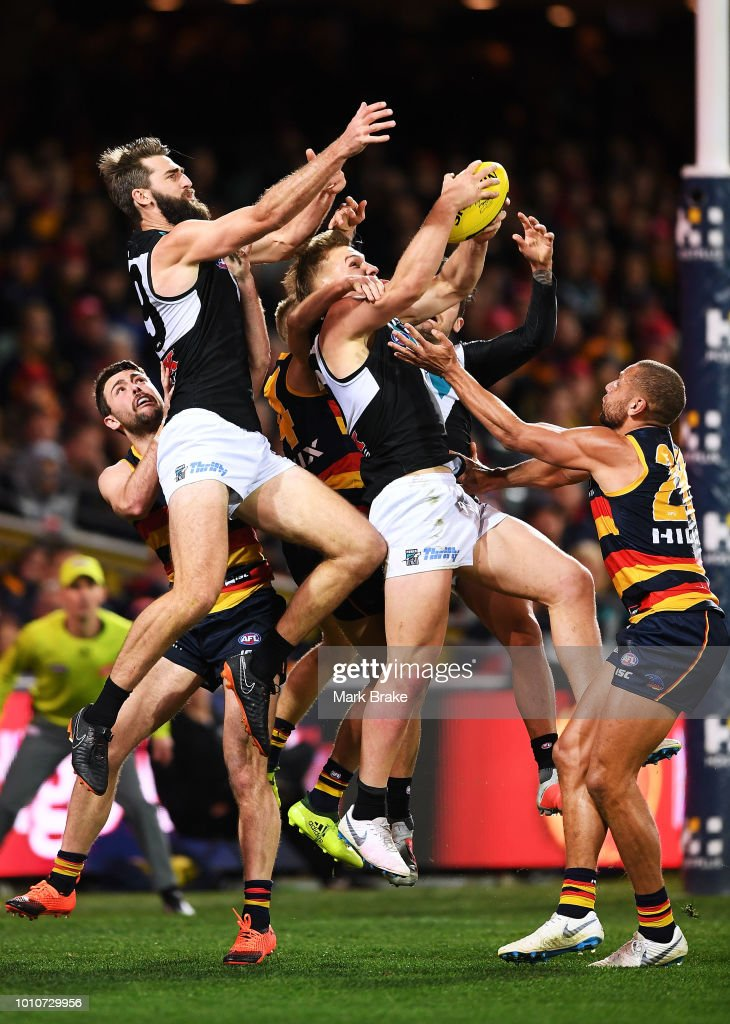 Ollie Wines of Port Adelaide marks in front of Justin Westhoff of Port Adelaide and Cam Ellis-Yoleman of the Adelaide Crows during the round 20 AFL match between the Adelaide Crows and the Port Adelaide Power at Adelaide Oval on August 4, 2018 in Adelaide, Australia.