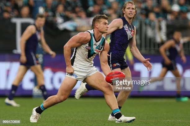 Ollie Wines of the Power handballs during the round 17 AFL match between the Fremantle Dockers and the Port Adelaide Power at Optus Stadium on July...