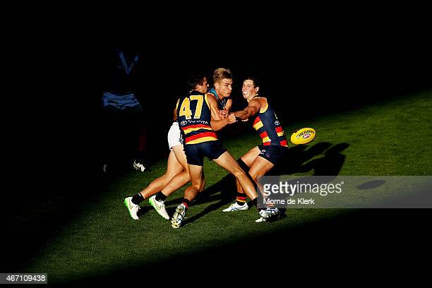 Ollie Wines of the Power is tackled by Jake Kelly and Luke Brown of the Crows during the NAB Challenge AFL match between the Port Adelaide Power and...