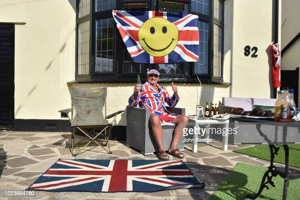 Olly Browne wears a Union Jack Jacket and Cap as he enjoys a social distancing VE day street party from his front garden on May 08 2020 in Leigh on...