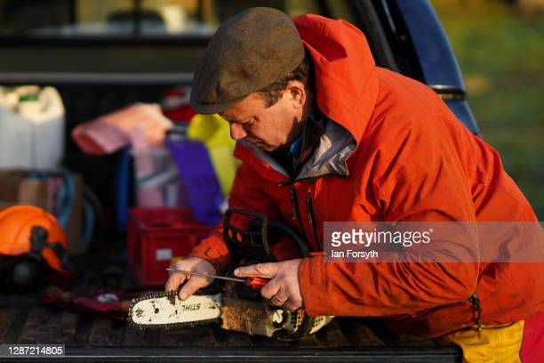 Olly Combe owner of York Christmas Trees sharpens his chain saw as he prepares to fell a 20 foot Nordmann Fir tree to be sent to stand outside 10...