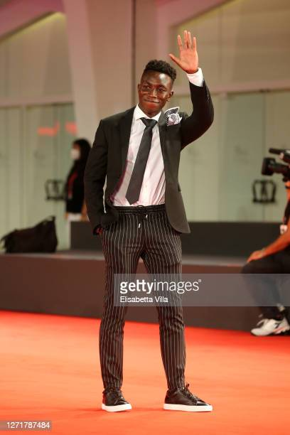"""Olly Sholotan walks the red carpet ahead of the movie """"Run Hide Fight"""" at the 77th Venice Film Festival on September 10, 2020 in Venice, Italy."""