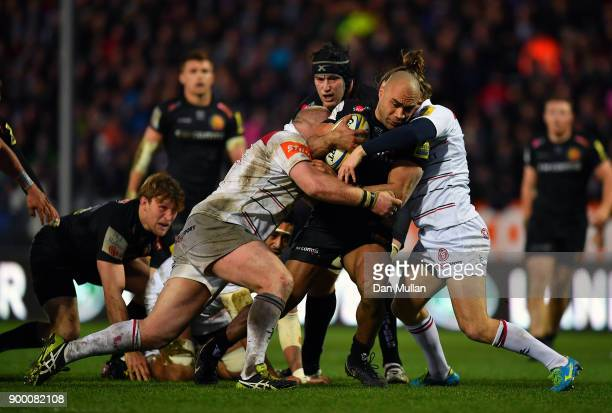 Olly Woodburn of Exeter Chiefs is tackled by Dan Cole and Sam Harrison of Leicester Tigers during the Aviva Premiership match between Exeter Chiefs...