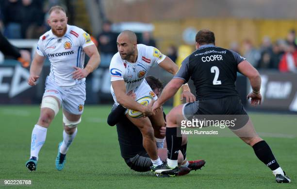 Olly Woodburn of Exeter Chiefs is tackled by Michael Young and Kyle Cooper of Newcastle Falcons during the Aviva Premiership match between Newcastle...