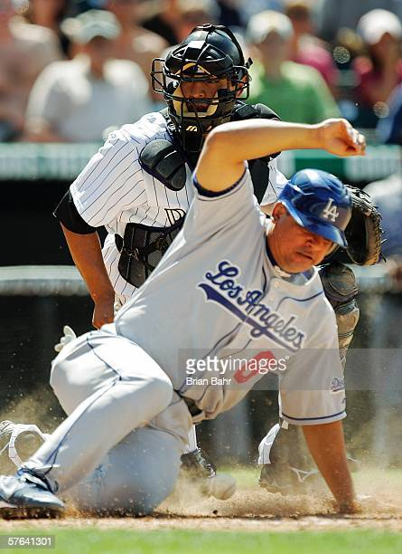 Olmedo Saenz of the Los Angeles Dodgers slides safely home to give the Dodgers a tworun lead as catcher Miguel Ojeda of the Colorado Rockies loses...