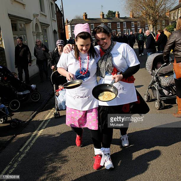 Olney Pancake race two young women competing in this annual three legged event in Olney Buckinghamshire England 2011