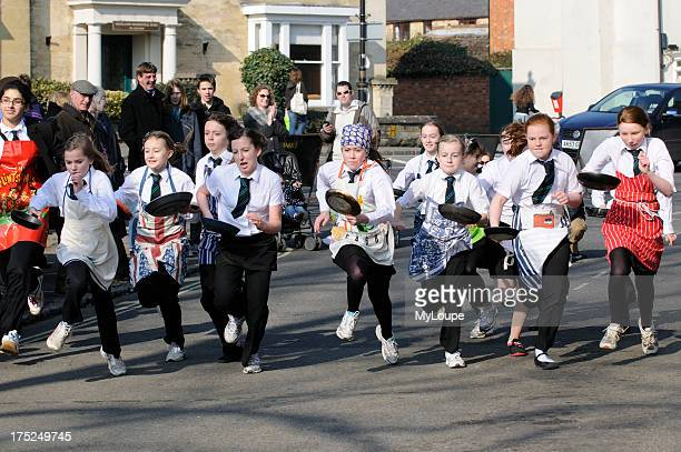 Olney Pancake race young girls competing in this annual event in Olney Buckinghamshire England 2011