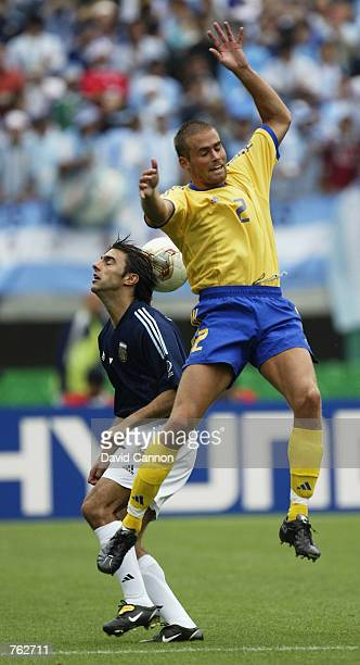 Olof Mellberg of Sweden and Claudio Lopez of Argentina both miss the ball during the FIFA World Cup Finals 2002 Group F match played at the Miyagi...