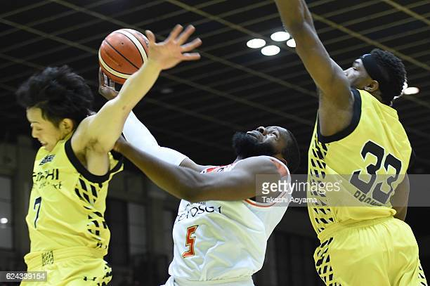 Olu Ashaolu of the SANEN NeoPhoenix tries to shoot under pressure from Takashi Ito and Ira Brown of the SunRockers during the B League match between...
