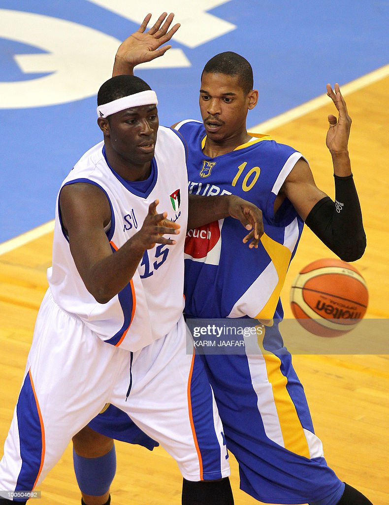 Olumide Oyedeji of Jordan's ASU club (L) passes the ball as he is challenged by C.J. Giles of Lebanon's Al-Riyadi during their 21st FIBA Asia Champions Cup basketball match at Al-Gharafa Indoor Stadium in Doha on May 25, 2010.