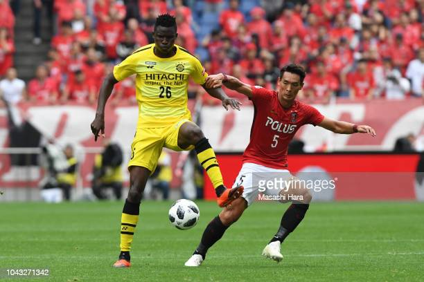 Olunga of Kashiwa Reysol and Tomoaki Makino of Urawa Red Diamonds compete for the ball during the JLeague J1 match between Urawa Red Diamonds and...