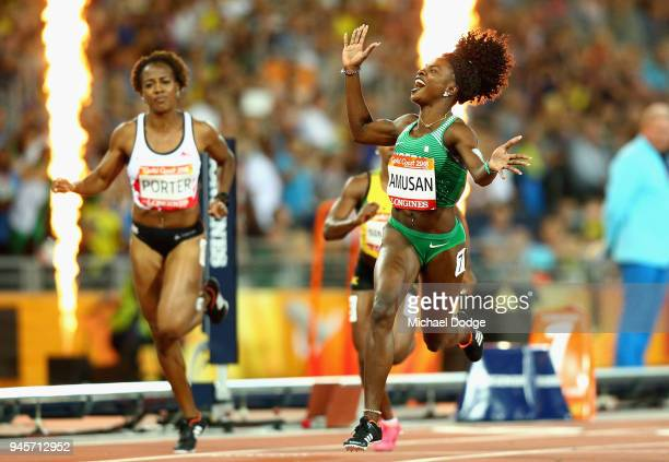 Oluwatobiloba Amusan of Nigeria celebrates as she crosses the line to win gold ahead of Tiffany Porter of England in the Women's 100 metres hurdles...