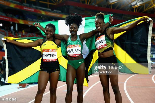 Oluwatobiloba Amusan of Nigeria celebrates winning gold with silve rmedalist Danielle Williams of Jamaica and bronze medalist Yanique Thompson of...
