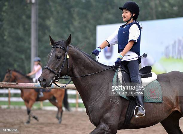 """Oly-2008-CHN-equestrian"""" by Fancois Bougon A young jockey enjoys the galloping pace of her horse at an equestrian club in Shunyi, on the outskirts of..."""