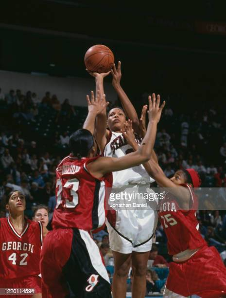 Olympia Scott, Forward for the University of Stanford Cardinal drives for the hoop over Tracy Henderson and Kedra Holland of the University of...
