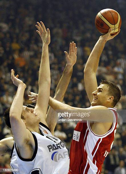 Olympiacos Athens player Andrija Zizic, right, shoots the ball over Kosta Perovic, left, from Partizan Belgrade, during the TOP 16 group E Euroleague...