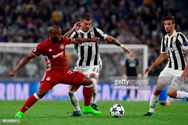 Olympiacos' Brazilian forward Seba fights for the ball with Juventus' midfielder from Italy Stefano Sturaro and Juventus' midfielder from Uruguay...