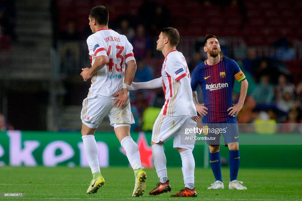 Olympiacos' defender Dimitris Nikolaou (L) celebrates his goal as Barcelona's Argentinian forward Lionel Messi looks on during the UEFA Champions League group D football match FC Barcelona vs Olympiacos FC at the Camp Nou stadium in Barcelona on Ocotber 18, 2017. / AFP PHOTO / Josep LAGO