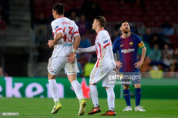 Olympiacos' defender Dimitris Nikolaou celebrates his goal as Barcelona's Argentinian forward Lionel Messi looks on during the UEFA Champions League...