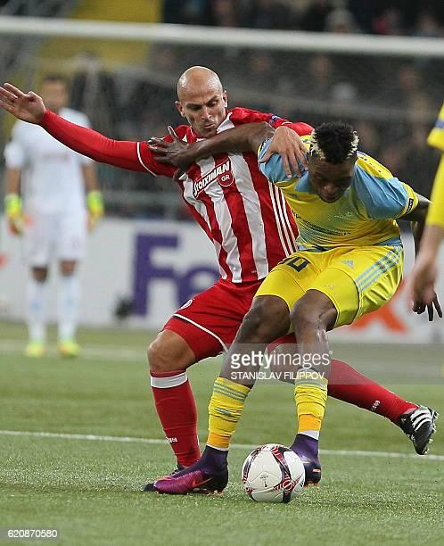Olympiacos' Esteban Cambiasso and FC Astana's Congolese forward Junior Kabananga vie for the ball during the UEFA Europa League group B football...