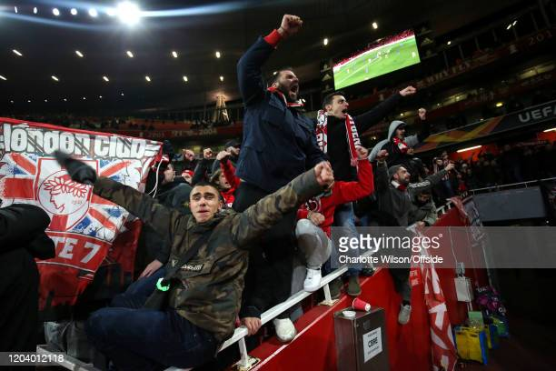 Olympiacos fans celebrate their victory during the UEFA Europa League round of 32 second leg match between Arsenal FC and Olympiacos FC at Emirates...