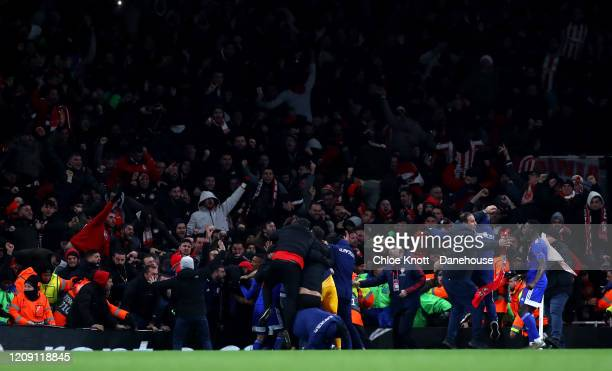 Olympiacos FC fans enterthe pitch during the UEFA Europa League round of 32 second leg match between Arsenal FC and Olympiacos FC at Emirates Stadium...