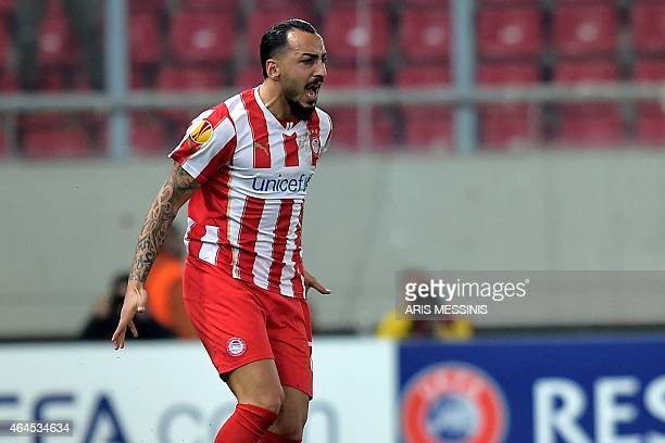 Olympiacos' forward Kostas Mitroglou celebrates after scoring a goal during the UEFA Europa League Round of 32 football match Olympiacos vs Dnipro in...