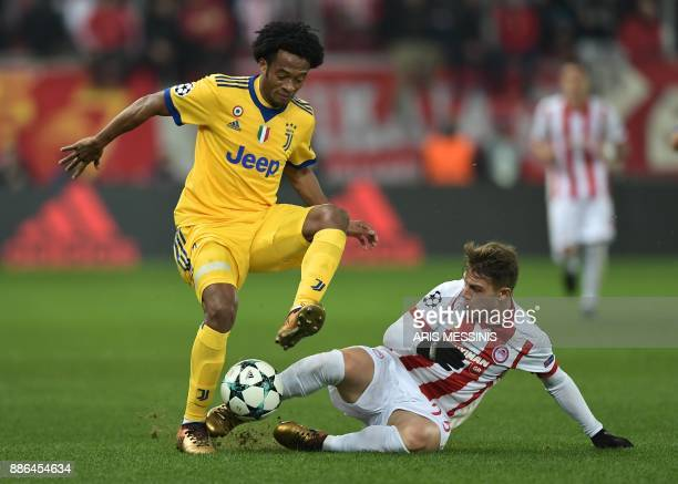Olympiacos' forward Leonardo Koutris vies for the ball with Juventus' forward from Colombia Juan Cuadrado during the UEFA Champions League group D...