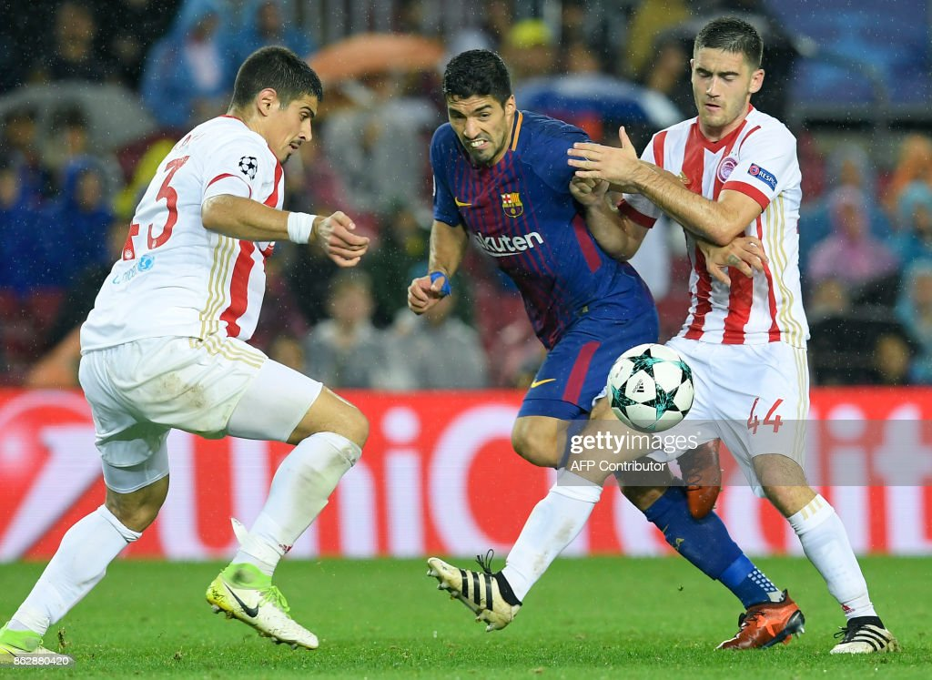 Olympiacos' Greek defender Dimitris Nikolaou (L) and Olympiacos' Serbian midfielder Sasa Zdjelar (R) vie with Barcelona's Uruguayan forward Luis Suarez during the UEFA Champions League group D football match FC Barcelona vs Olympiacos FC at the Camp Nou stadium in Barcelona on Ocotber 18, 2017. /