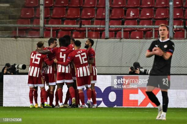 Olympiacos' Greek midfielder Andreas Bouchalakis celebrates with teammates after scoring a goal during the UEFA Europa League round of 32 first leg...