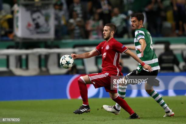 Olympiacos' Greek midfielder Kostas Fortounis fights for the ball with Sporting's defender Andre Pinto from Portugal during the UEFA Champions League...
