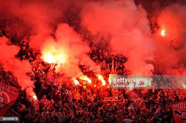 Olympiacos Piraeus fans light and throw flares during the Greek Super League football match against Panathinaikos at Karaiskaki stadium in Piraeus...