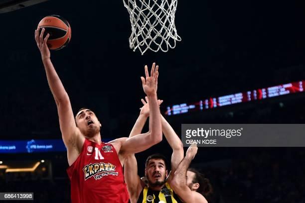 Olympiacos' Serbian center Nikola Milutinov jumps for the basket next to Fenerbahce's Serbian forward Nikola Kalinic during the first place...