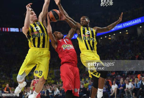 Olympiacos's Erick Green jumps for the basket as Fenerbahce's Bogdan Bogdanovic and James Nunnally try to block him during the first place basketball...