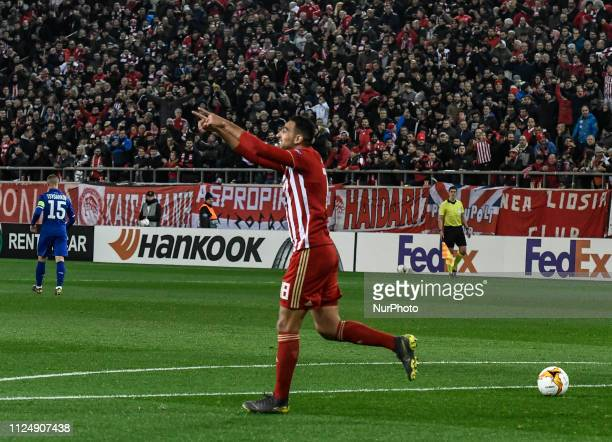Olympiakos' Ahmed Hassan celebrates with a teammate after scoring the opening goal during the Europa League round of 32 soccer match between...