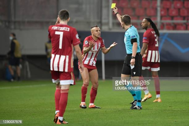 Olympiakos' Brazilian defender Rafinha is given a yellow card by the referee during the UEFA Champions League Group C football match between...