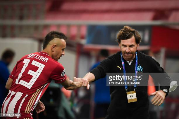 Olympiakos' Brazilian defender Rafinha touches fists with Marseille's Portuguese coach Andre Villas Boas during the UEFA Champions League Group C...