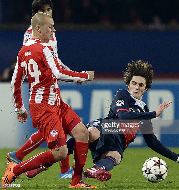 Olympiakos' forward Vladimir Weiss is tackled by Paris SaintGermain's French midfielder Adrien Rabiot during an UEFA Champions League group C...