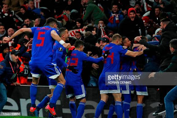 Olympiakos' Frenchborn Moroccan striker Youssef ElArabi and teammates join supporters as he celebrates after scoring their late goal in extra time...