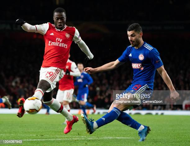 LONDON ENGLAND FEBRUARY Olympiakos' Giorgos Masouras is tackled by Arsenal's Nicolas Pepe during the UEFA Europa League round of 32 second leg match...