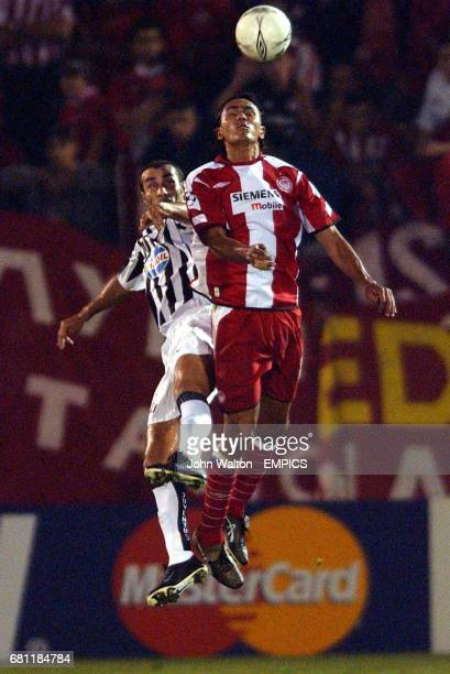 Olympiakos' Giovanni battles for possession of the ball with Juventus' Paolo Montero