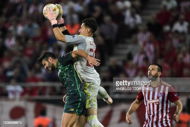 Olympiakos' Greek goalkeeper Andreas Gianniotis fights for the ball with Real Betis' Spanish defender Antonio Barragan during the UEFA Europa League...