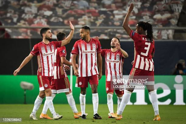 Olympiakos' Greek midfielder Georgios Masouras celebrates with teammates after scoring a goal during the UEFA Champions League Group C first-leg...