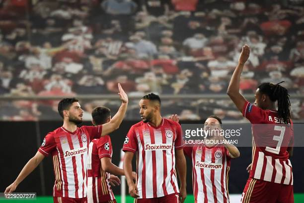 Olympiakos' Greek midfielder Georgios Masouras celebrates with teammates after scoring a goal that will be disallowed during the UEFA Champions...