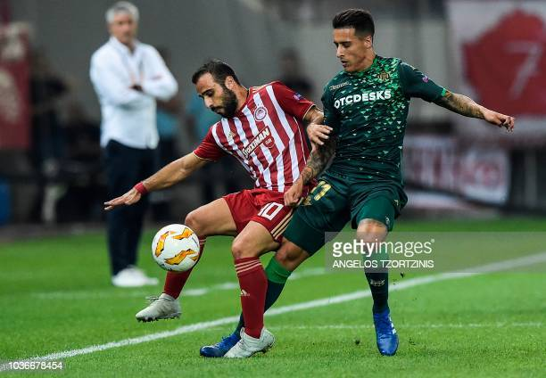 Olympiakos' Greek midfielder Ioannis Fetfatzidis fights for the ball with Real Betis' Spanish forward Cristian Tello during the UEFA Europa League...