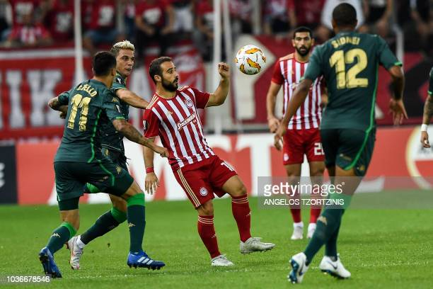 Olympiakos' Greek midfielder Ioannis Fetfatzidis fights for the ball with Real Betis' Spanish forward Cristian Tello and Real Betis' Brazilian...