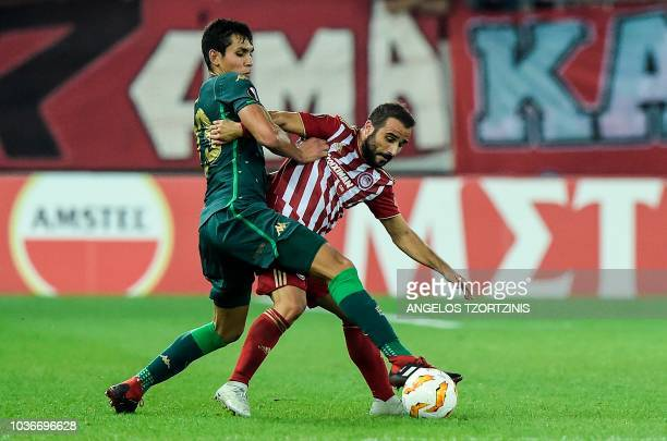 Olympiakos' Greek midfielder Ioannis Fetfatzidis fights for the ball with Real Betis' Defender Aissa Mandi during the UEFA Europa League Group F...